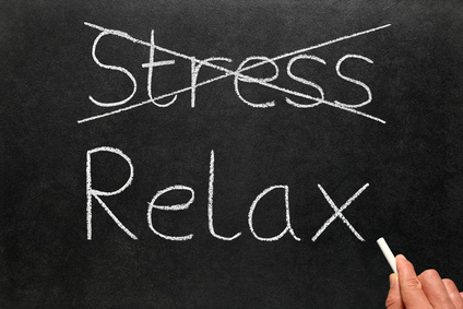Crossing out stress and writing relax on a blackboard.